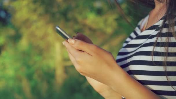 Nahaufnahme von Mädchenhänden mit dem Handy im grünen Sommerpark. 4k