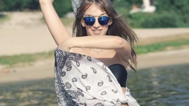 Šťastná dívka v černých plavkách pózuje v řece s pareo. Pomalu