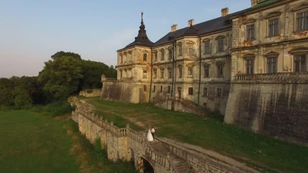 Letecký pohled: krásné svatební pár na schody na hrad pozadí. 4k