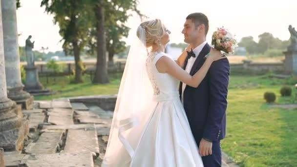 Profil šťastný svatební pár něžně objímala nedaleko hradu. 4k