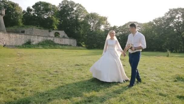 Hochzeitspaar geht in der Nähe des alten Schlosses spazieren