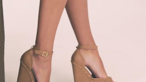 Stylish shoes on female legs. Slowly
