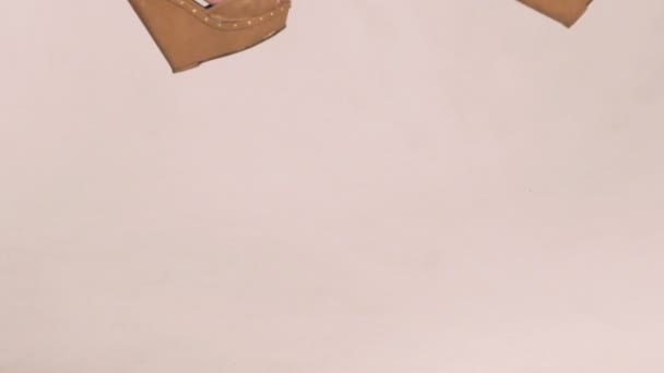 Girls legs in heels moving in air on white background . Slow motion
