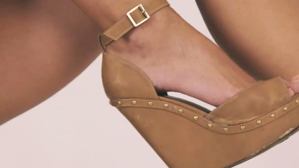 Close up girls legs in heels moving in air on white background . Slow motion