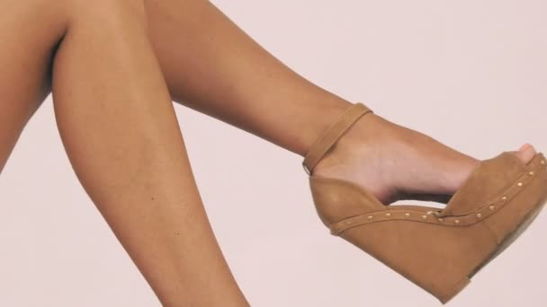 Girls long legs in heels moving in air on white background . Slow motion
