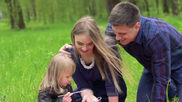 Happy young family, baby drawing the Easter egg in a park