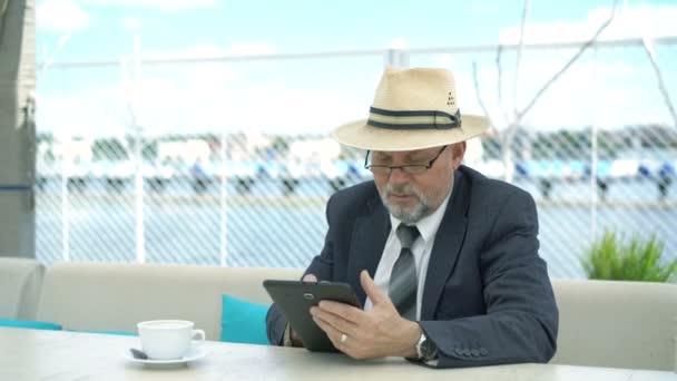 Freundlich, gut aussehend Greis mit Tablet-Computer im Café. 4k