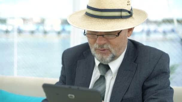Nahaufnahme des alten Mannes mit Tablet und suchen auf Armbanduhr am Tisch. 4k
