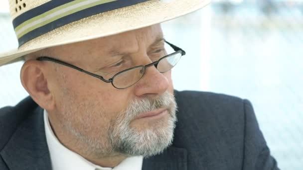Detailní záběr starého muže v klobouku, oblek a brýle hledá vážné stranou. 4k