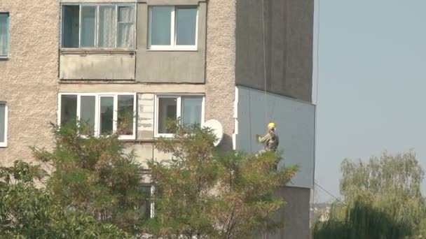 Builder working on a rope for restoring a building