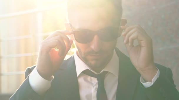 Portrait of man removing his sunglasses and looking on camera in dazzle. Slowly