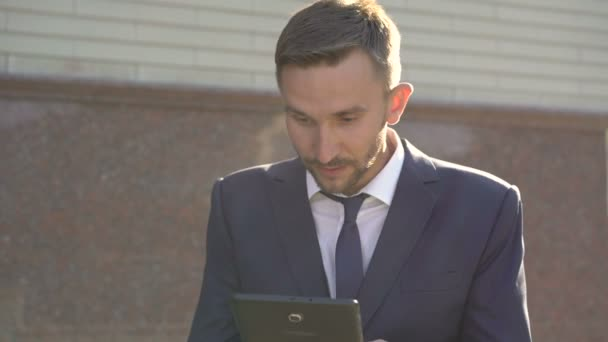 Businessman in suit using tablet and expressing emotions of win. 4K