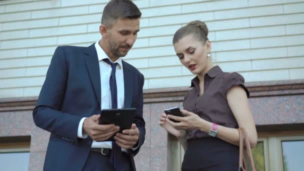 Businessman and woman using digital tablet and mobile phone near office. 4K