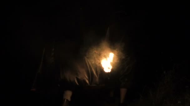 People in black coats with fire in hands going in dark forest. Slowly