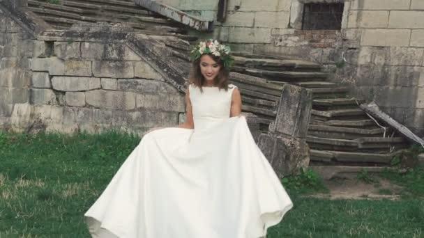 Chytré nevěsta ve svatebních šatech chůzi a pózování. Zpomalený pohyb