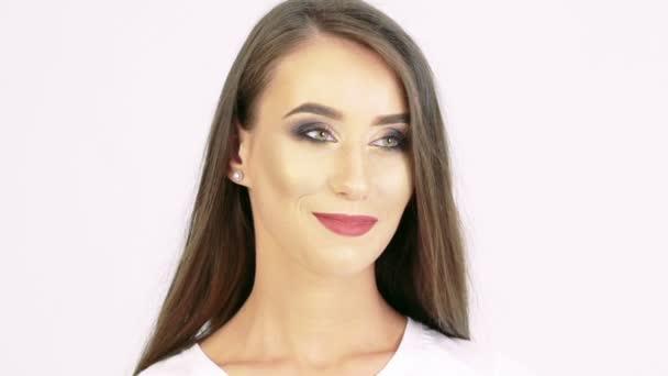 Portrét usmívající se dívka dívá stranou na béžové pozadí. Pomalu