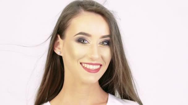 Portrét usmívající se dívka na kameru na béžové pozadí. Pomalu