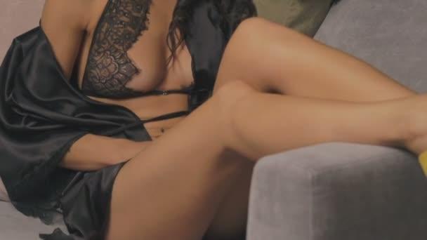 Hezká žena ve spodním prádle hladil její tělo na posteli. Pomalu