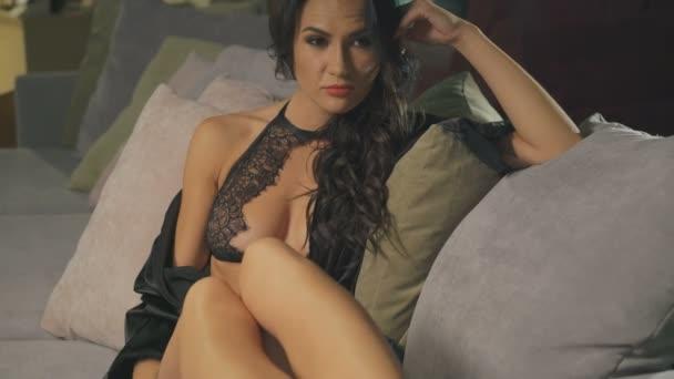 Szexi nő erotikus csipke fehérnemű a kanapén fedett pihenő. 4k