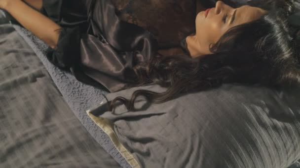 Verführerische Frau in Dessous auf dem Bett liegend und Körper berührt. 4k