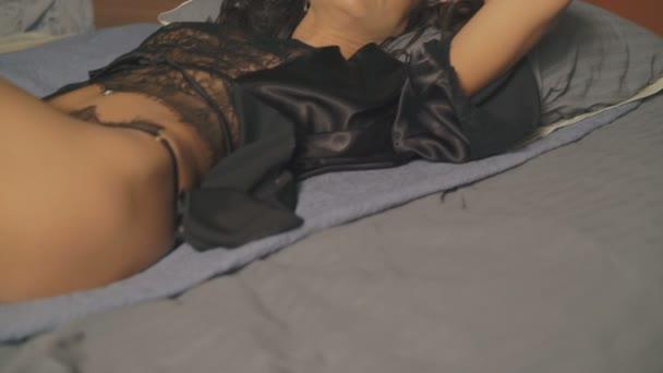 Svůdná žena v pradlo ležící na posteli. 4k