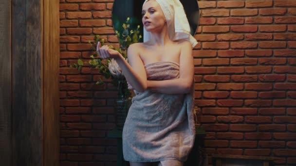 Meztelen nő törülközőben pózol a kamera előtt egy szobában.