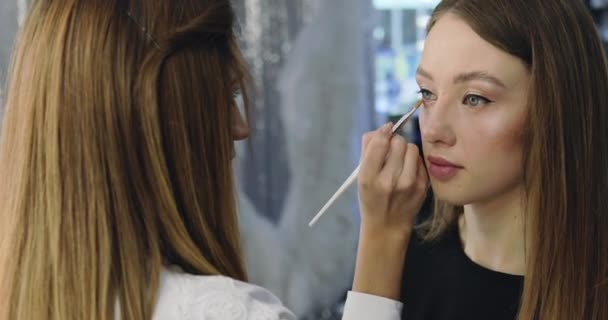 Closeup of girl with perfect nude make-up and the artist. Make-up process for beautiful young model