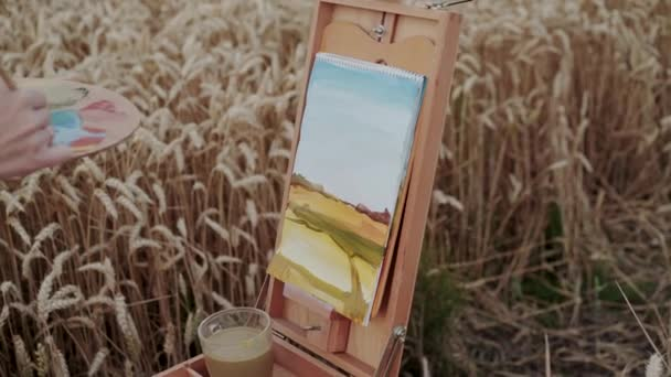 Female hand painting a landscape with brush and watercolors among golden wheat