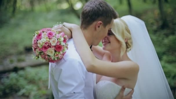 Beautiful wedding couple kissing in a forest