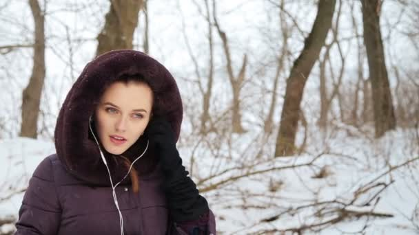 Krásná dívka poslouchá hudbu v zimě