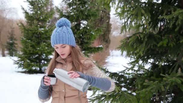 girl drink hot tea in a thermos in snowy forest