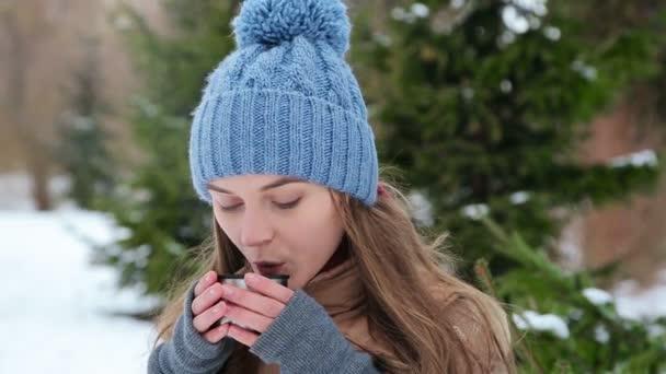 krásná dívka pití z termosky zimní