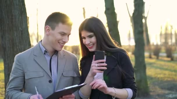 Funny business partners in park using smartphone