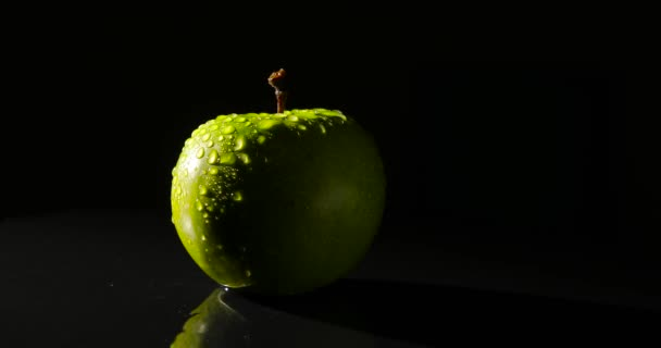 A green apple rotating on a black background