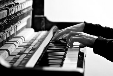 hands pianist on a old piano keyboard in black and white
