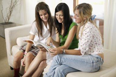 Teenage students reading school book