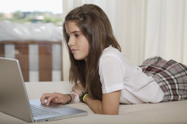 Teenager studying with laptop