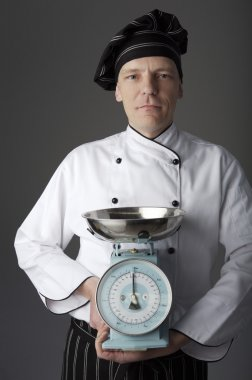 Chef holding old weigh scales