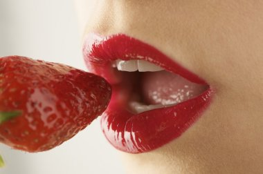 female mouth eating strawberry