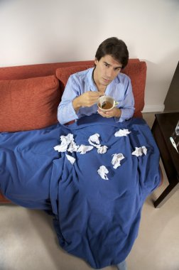 Sick man with tissues drinking tea