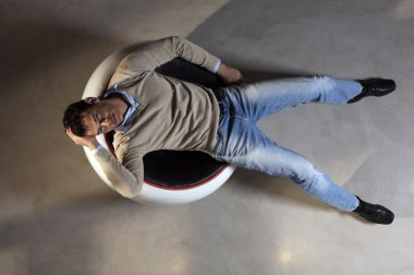 Man lying down on round chair