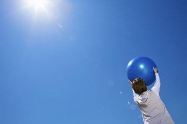 An elderly woman holding an exercise ball