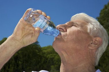 An elderly man drinking from bottle