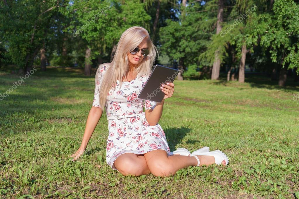 Girl sitting on the grass in the park with tablet