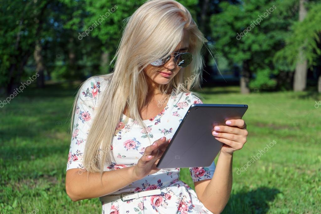 Girl sitting in the park and use a tablet.