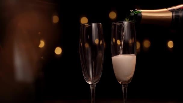 Detailní záběr barmana nalévání šampaňského do sklenic na černém pozadí, sklo má hodně pěny a bublin. Zpomalený pohybu.Koncepce dovolené, Nový rok, Vánoce, narozeniny.