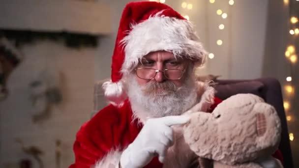 Vicces Mikulás ül az ő rocker évben karácsonyfa Teddy medve karácsonyi szellem, ünnepek és ünnepségek koncepció 4k felvételek