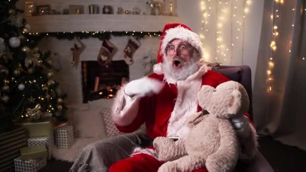 Legrační Santa Claus sedí v jeho rocker rok vánoční strom s medvídek vánoční duch, svátky a oslavy koncept 4k záběry