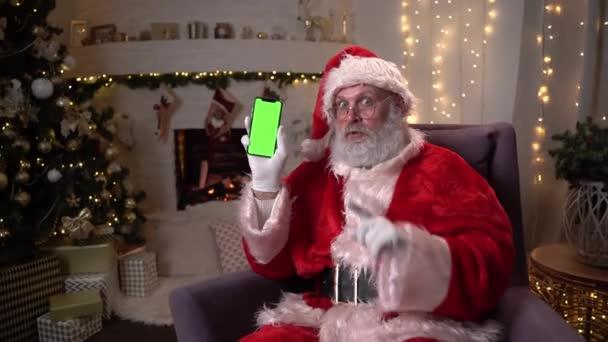 Boldog Mikulás ül széken közel karácsonyfa és kandalló, mutatja a mobiltelefon zöld képernyőn. Karácsonyi szellem, ünnepek és ünnepségek koncepció 4k felvételek