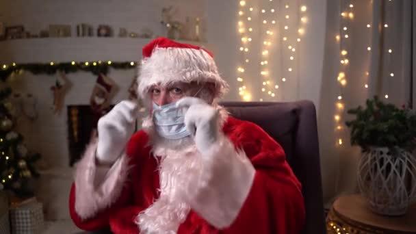 Lustige Weihnachtsmänner in einer Schutzmaske sitzen in einem Stuhl am Kamin und Weihnachtsbaum. Covid 19, Schutz gegen Coronavirus.